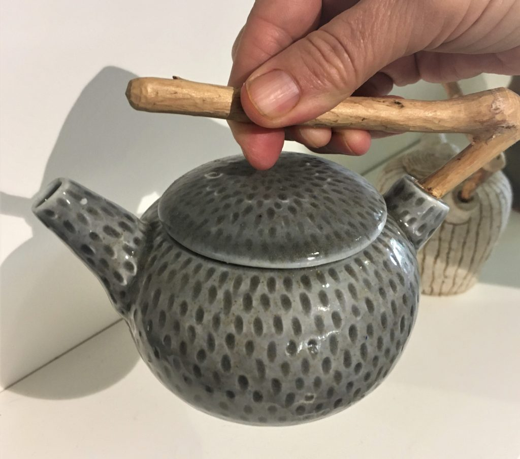 Small teapot with spots and wooden handle